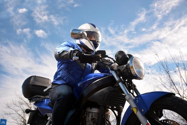 Motociclista com capacete azul passando por uma estrada Foto Premium