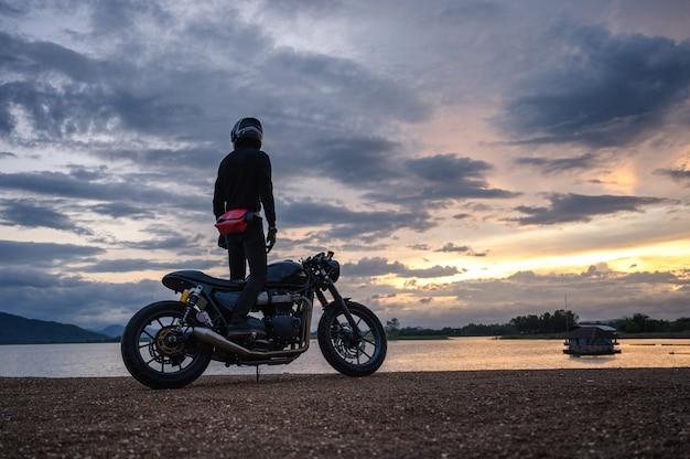 Motociclista em pé na bicicleta grande vintage com céu no reservatório Foto Premium