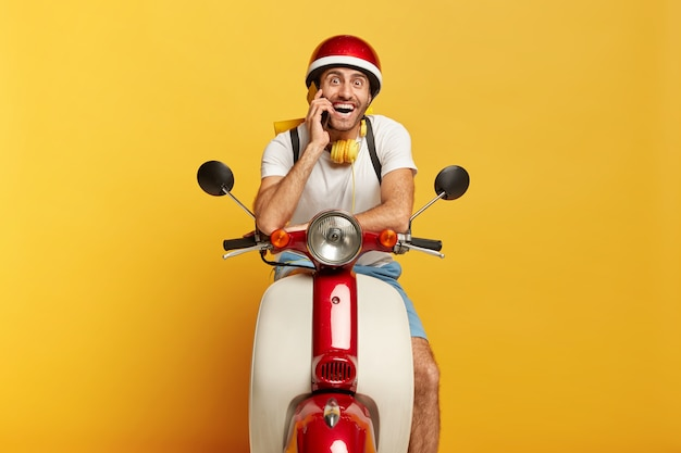 Motociclista feliz posa no próprio transporte rápido, liga para o cliente via smartphone, viaja de longa distância, usa capacete, fones de ouvido estéreo no pescoço, sorri para a câmera motorista masculino dirige scooter Foto gratuita