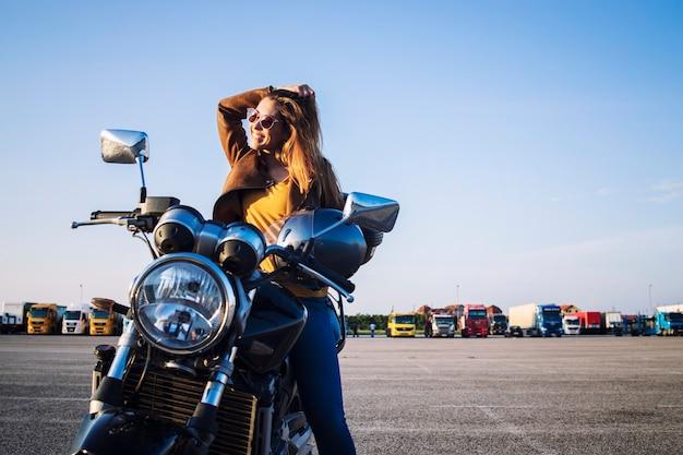 Motociclista feminina em uma jaqueta de couro, sentada em uma moto retrô e sorrindo Foto gratuita