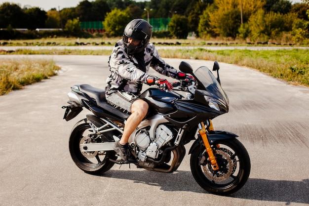 Motociclista na moto estacionada na estrada Foto gratuita