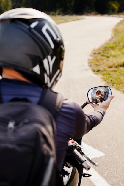 Motociclista que fixa o espelho retrovisor de moto Foto gratuita