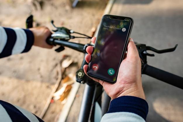 Motociclista, segurando, smartphone, com, entrante, chamada Foto Premium