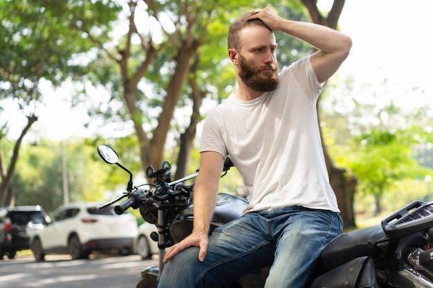 Motociclista sério, apoiando-se na moto quebrada Foto gratuita