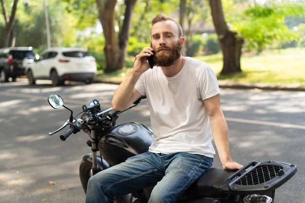 Motociclista sério chamando assistência na estrada Foto gratuita