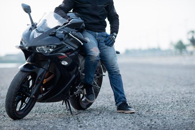 Motorbiker bonito com capacete nas mãos da motocicleta Foto gratuita