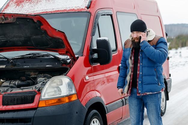 Motorista chama assistência técnica na estrada no inverno Foto Premium