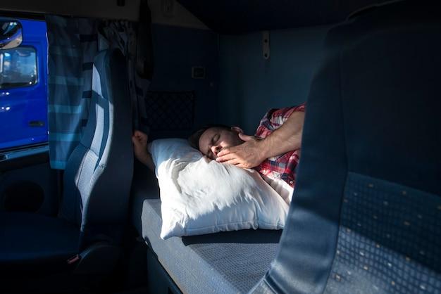 Motorista de caminhão bocejando e acordando em sua cabine na parada de caminhões Foto gratuita
