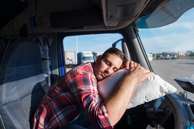 Motorista de caminhão cansado apoiado no volante dormindo em seu travesseiro Foto gratuita