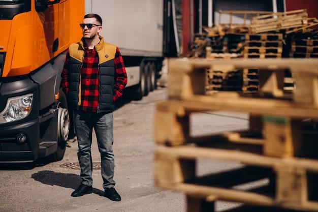 Motorista de caminhão de homem bonito em pé ao lado do caminhão Foto gratuita