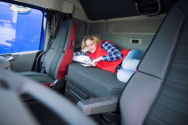 Motorista de caminhão deitado na cama em sua cabine se comunicando com sua família via tablet Foto gratuita