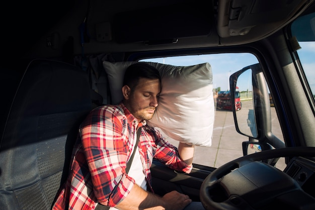 Motorista de caminhão dormindo na cabine de seu caminhão devido a longas distâncias e excesso de trabalho Foto gratuita