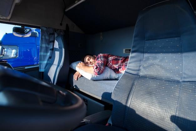 Motorista de caminhão dormindo na cama dentro do interior da cabine do caminhão Foto gratuita
