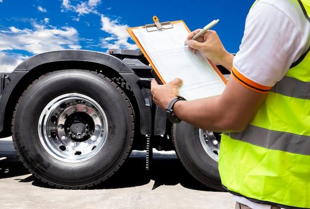 Motorista de caminhão está escrevendo na área de transferência com inspeção de pneus de caminhão. Foto Premium