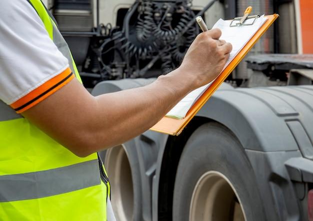 Motorista de caminhão está escrevendo na área de transferência com inspecionando os caminhões. Foto Premium