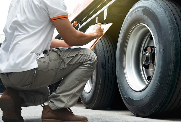 Motorista de caminhão está inspecionando a segurança do caminhão de rodas. Foto Premium
