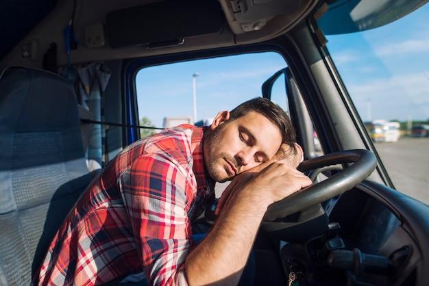 Motorista de caminhão exausto adormecendo no volante Foto gratuita