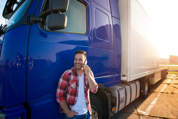 Motorista de caminhão parado ao lado de seu caminhão e falando ao telefone. Foto Premium