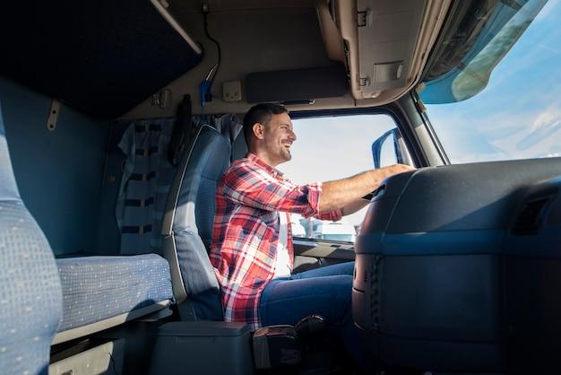 Motorista de caminhão profissional de meia-idade feliz com roupas casuais, dirigindo um caminhão na rodovia Foto gratuita