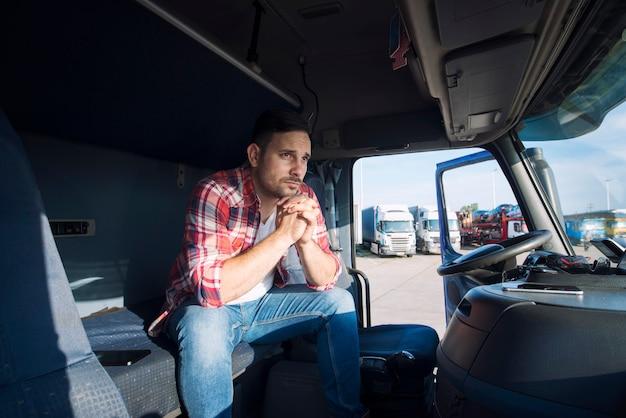 Motorista de caminhão sentado em sua cabine pensando em sua família Foto gratuita