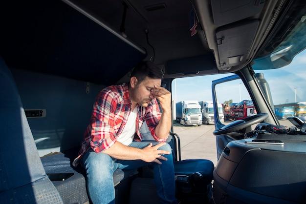 Motorista de caminhão sentado em sua cabine sentindo-se preocupado e chateado Foto gratuita