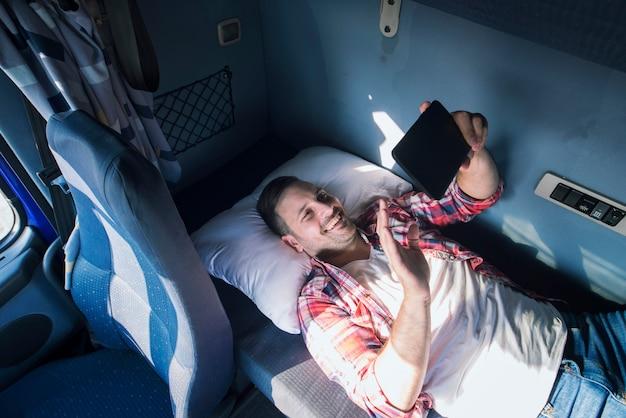 Motorista de caminhão separado de sua família deitado no chão de sua cabine e acenando para sua esposa e filhos por meio de um tablet Foto gratuita