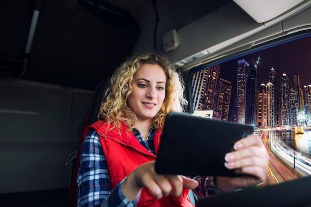Motorista de caminhão usando dispositivo de navegação gps para navegar pelo grande tráfego da cidade para chegar ao destino Foto gratuita