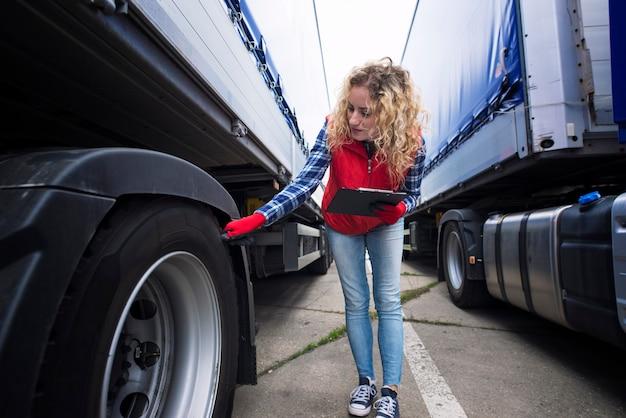 Motorista de caminhão verificando os pneus do veículo e inspecionando o caminhão antes do passeio Foto gratuita