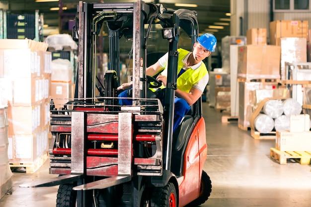 Motorista de empilhadeira em colete protetor dirigindo empilhadeira no armazém da empresa de expedição de mercadorias Foto Premium