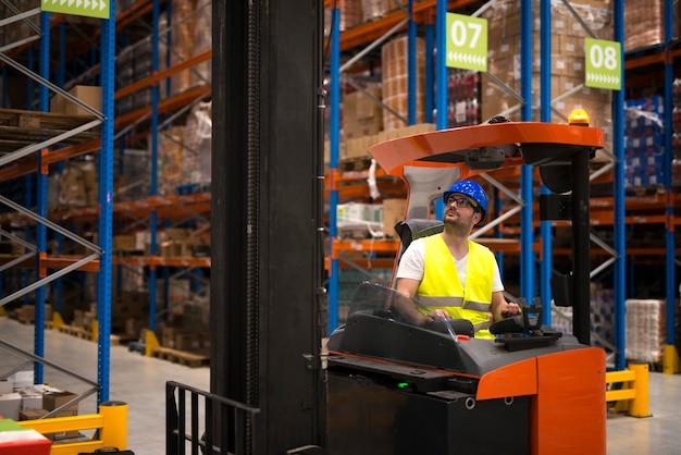Motorista de empilhadeira realocando e levantando mercadorias em um grande centro de armazém Foto gratuita