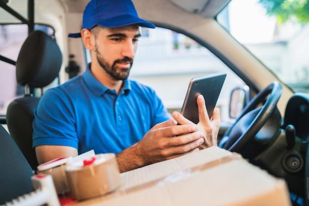 Motorista de homem entrega usando tablet digital. Foto Premium
