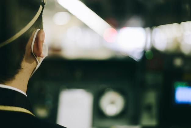 Motorista de trem com máscara na cabine de um trem moderno. local de controle interior do trem. Foto Premium