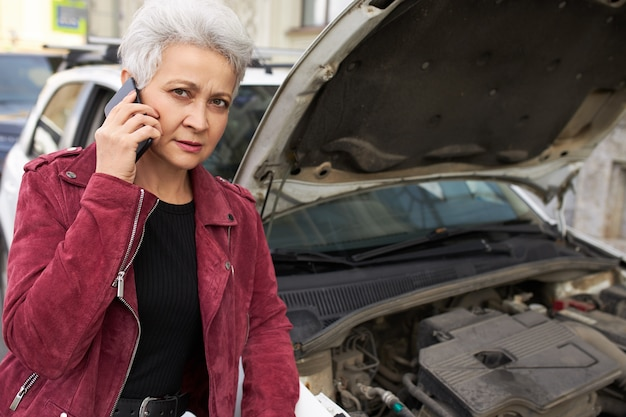 Motorista elegante e atraente de cabelos grisalhos, mulher madura em pé perto de seu carro branco quebrado com o capô aberto e falando ao telefone Foto gratuita