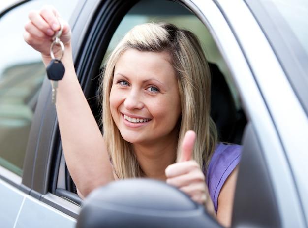 Motorista feminina animada mostrando uma chave depois bying um carro novo Foto Premium