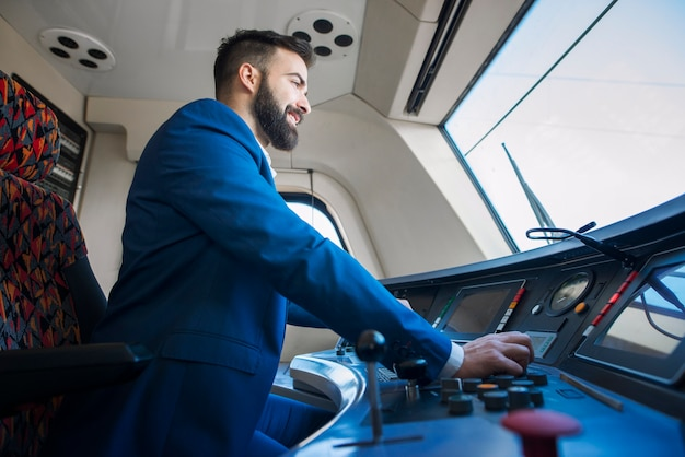 Motorista profissional sentado na cabine e operando em trem de alta velocidade Foto gratuita