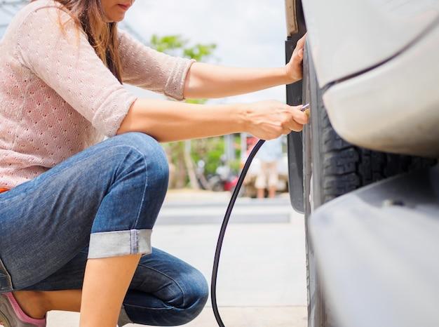 Motorista que verifica a pressão de ar e o ar de enchimento nos pneus. Foto Premium