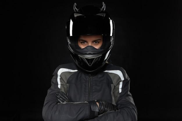 Motos esportivos, radicais, competição e adrenalina. atleta jovem ativa usando capacete de proteção e uniforme, vai participar de corridas de rua ou motocross, cruzando os braços sobre o peito Foto gratuita