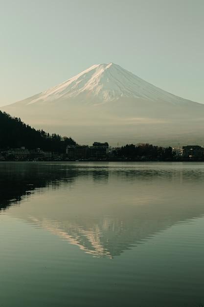 Mountain view de fuji e lago kawaguchiko no nascer do sol da manhã, estações do inverno no yamanachi, japão. paisagem com reflexo do horizonte na água. Foto Premium