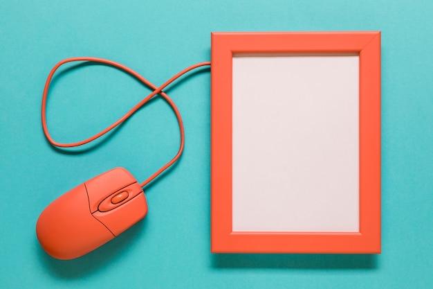 Mouse de computador e moldura vazia no fundo azul Foto gratuita