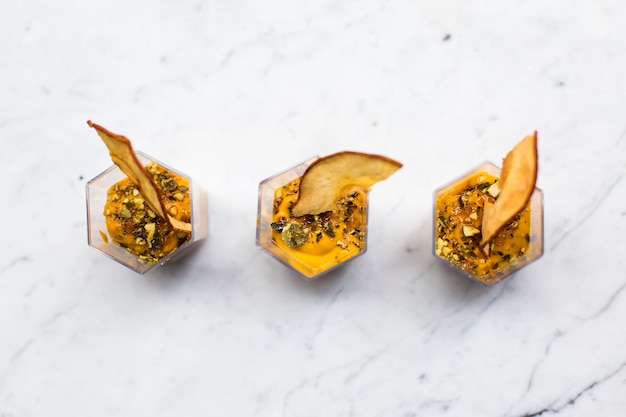 Mousse de abóbora caseira ou creme em copos polvilhados com canela Foto Premium