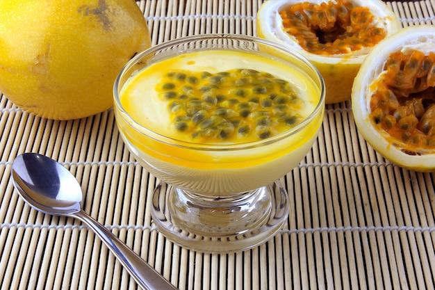 Mousse de maracujá de sobremesa em uma tigela de vidro na mesa de madeira rústica Foto Premium