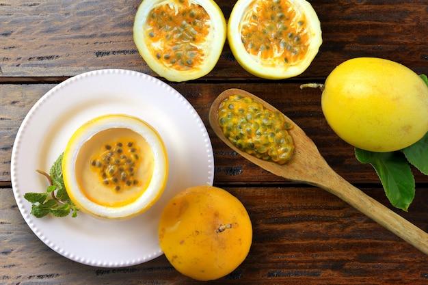 Mousse de maracujá sobremesa em casca de frutas no prato de mesa de madeira rústica Foto Premium