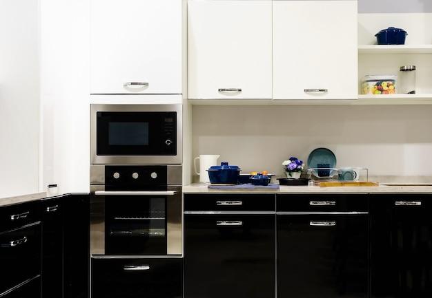 Móveis de cozinha com utensílios contemporâneos, como capô, fogão de indução preto e forno Foto Premium