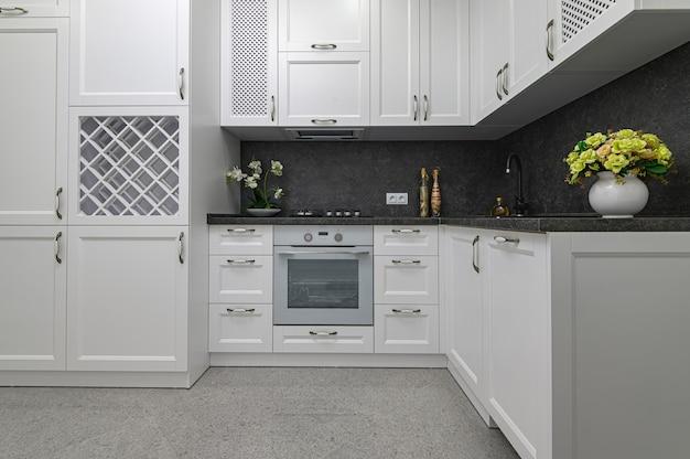 Móveis de madeira bem projetados em cozinha moderna em preto e branco em estilo clássico, vista frontal Foto Premium