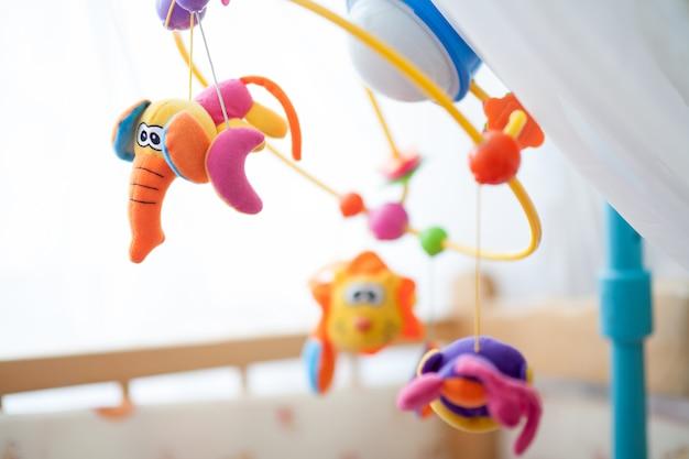 Móvel infantil sobre a cama, carrossel giratório com brinquedos Foto Premium