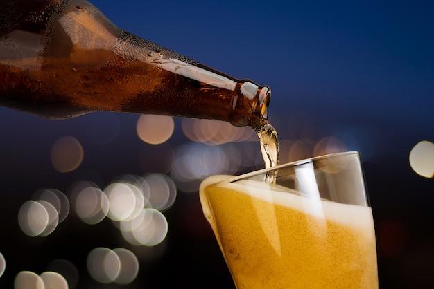Movimento, de, cerveja, despejar, de, garrafa, em, vidro, ligado, bokeh, luz, noturna, fundo Foto Premium