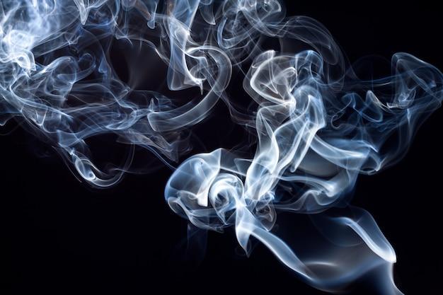 Movimento de fumaça azul e branco abstrato em fundo preto Foto Premium