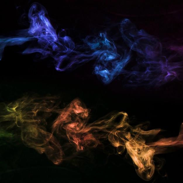 Movimento de fumaça colorida em fundo preto Foto gratuita
