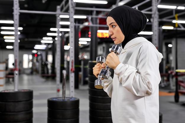 Muçulmana boxeadora em hijab branco sportswear em pé em pose de lutador com halteres, jovem árabe fazendo exercícios, levando um estilo de vida saudável. esporte em países islâmicos, conceitos de direitos das mulheres Foto Premium