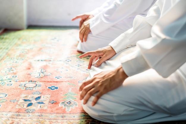 Muçulmanos orando em postura de tashahhud Foto gratuita